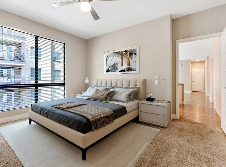 Model Bedroom with Bed and Cushioned Headboard Over Area Rug With Nightstands and Large Window