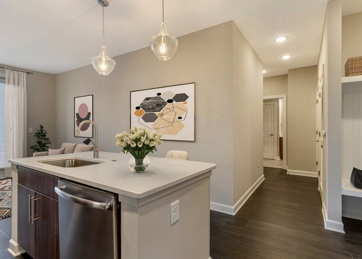 Fully equipped kitchen with modern lights, kitchen island, floral decorations, and framed art on the wall