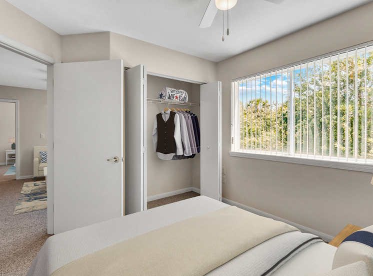 Virtually staged bedroom with large reach-in closet, multi speed ceiling fan, carpet flooring, and window for natural lighting