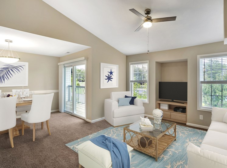 A virtually staged living room and dining room with gray walls with white trim, gray carpet, vaulted ceilings, sliding glass door with vertical blinds, and two windows with blinds.