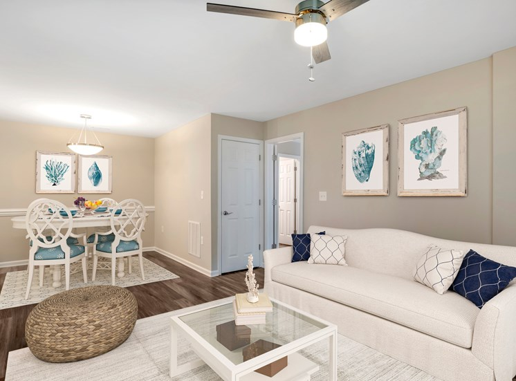 A virtually staged living and dining room with hardwood style flooring, gray walls with white trim, and a contemporary three blade ceiling fan.