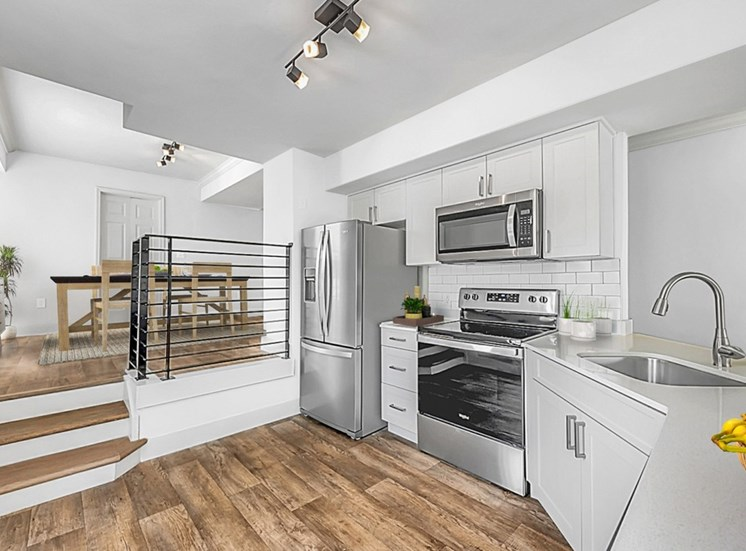 Open Kitchen with White Counters and Cabinets and Stainless Steel Appliances Next to Raised Dining Room
