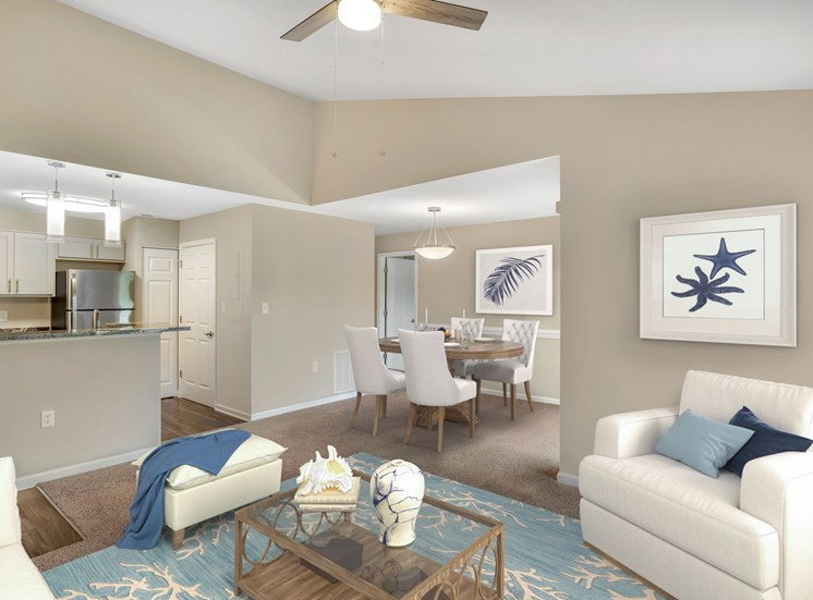 A virtually staged living and dining room with gray walls, gray carpet, vaulted ceilings and a contemporary three blade ceiling fan in the living room. The living room is beach theme with a white chair, white ottoman with blue throw blanket, a light blue rug patterned with white coral, and starfish artwork hanging on the wall.