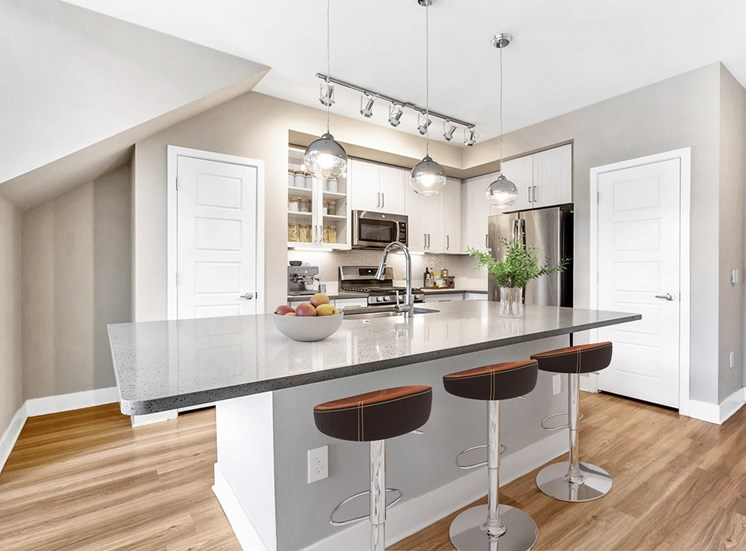 Model Kitchen with White Cabinets, Stainless Steel Appliances, Grey Counters and Breakfast Bar Next to Bar Stools Under Pendant Lighting