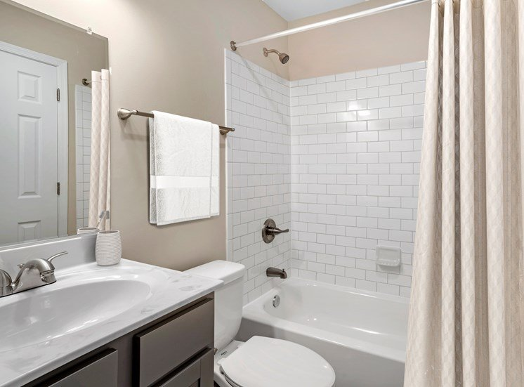 A vacant renovated bathroom with a single sink with marble countertops, gray ash cabinets below, brushed nickel plumbing fixtures, a single mounted mirror, one toilet, a towel bar, and a tub/shower combo with white subway tile surround.