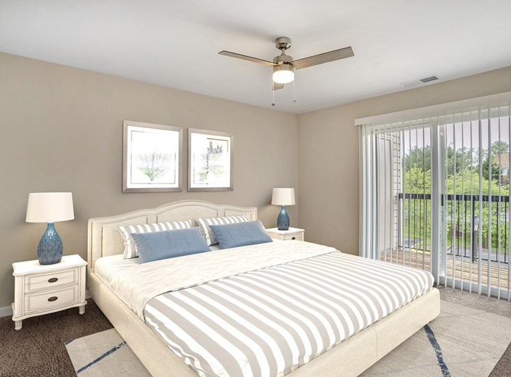 A virtually staged bedroom with gray walls with white trim, dark gray carpet throughout, and sliding glass door with vertical blinds leading to the outside patio/balcony area.
