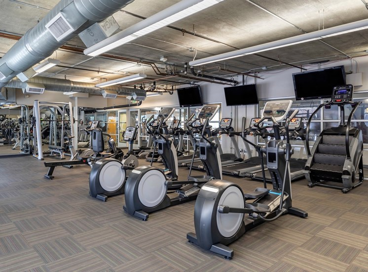 FITNESS CENTER WITH ROWS OF CARDIO EQUIPMENT INCLUDING TREADMILLS, ELLIPTICAL, BIKE, AND STAIR STEPPING MACHINES. FLATSCREEN TVS AND WEIGHT MACHINES IN THE BACKGROUND.