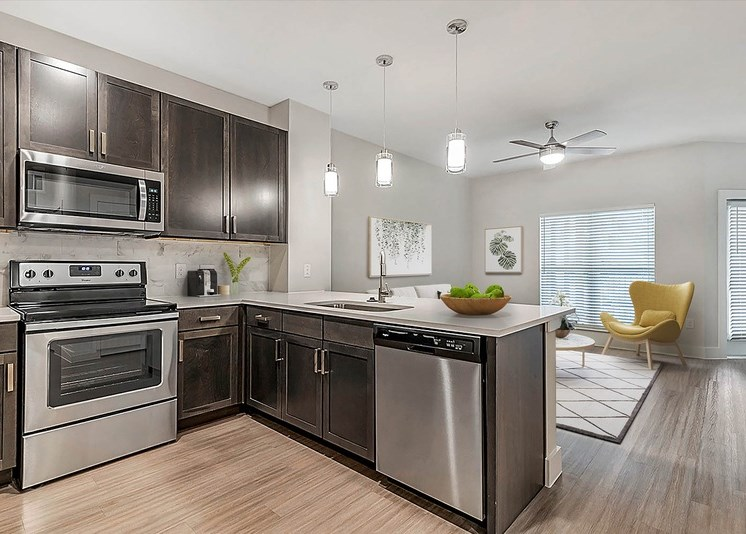 Fully equipped kitchen with view of kitchen, modern light fixtures, and brushed nickel appliances