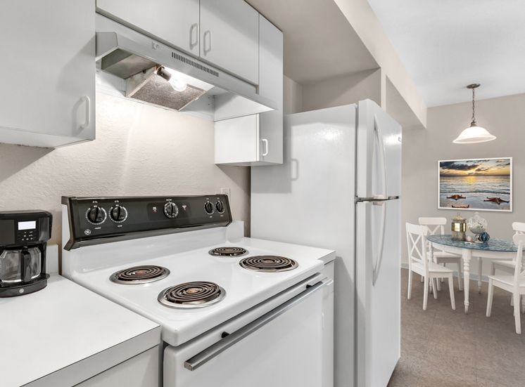 Kitchen with white appliances and furnished dining room in the background