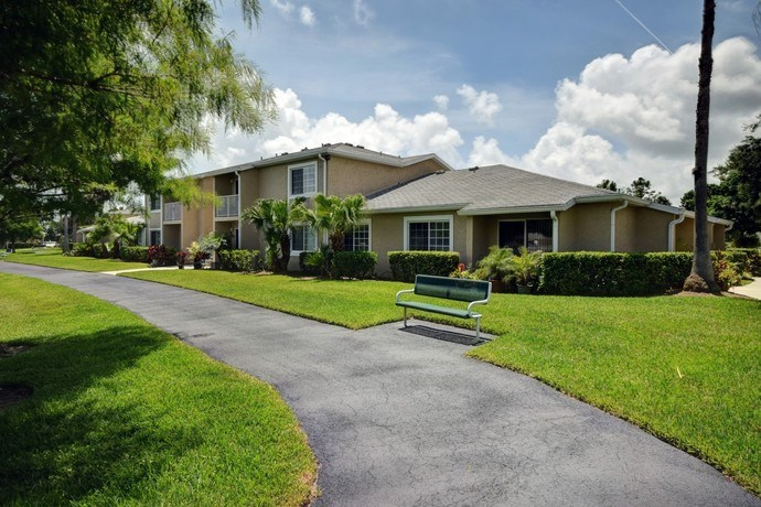 Walking Path Surrounded By Green Grass at River Park Place Apartments, Florida