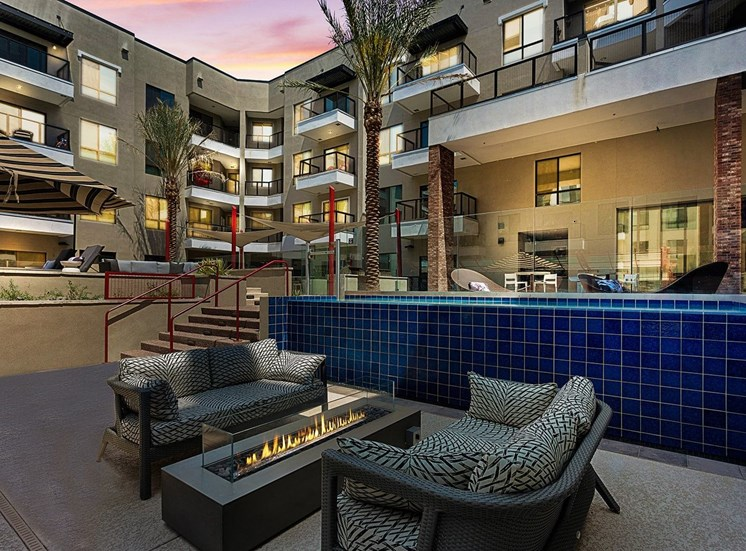 Sundeck with Fire Pit Next to Blue Tile Wall and Lounge Chairs with Building Exteriors in the Background