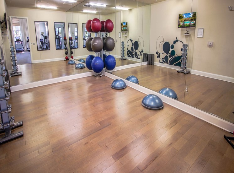 Fitness Room with Hardwood Style Flooring and Mirror Walls