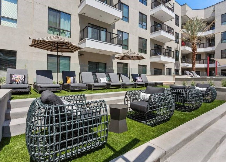 Courtyard with tanning lounge chairs, building exterior and balconies overlooking the area