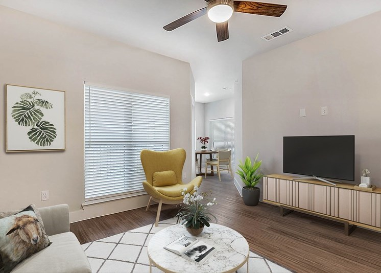 Living room with white and gray rug, accent chair, marble coffee table, and a television