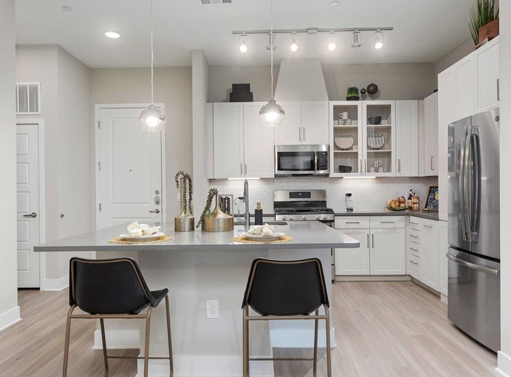 Open Layout with Modern Kitchen with Chairs Around Island, Gray Counter, White Cabinets and Stainless Steel Appliances