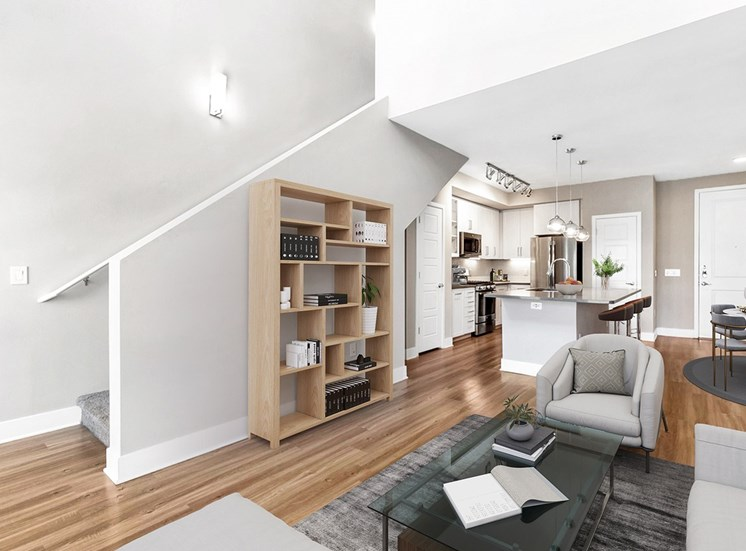 Bright Townhome Style Floor Plan with Contemporary Shelf, Armchair and Coffee Table on Area Rug with Kitchen in the Background
