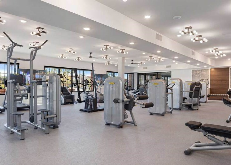 State of the art fitness center with strength training equipment, cardio equipment, and bay windows for natural lighting