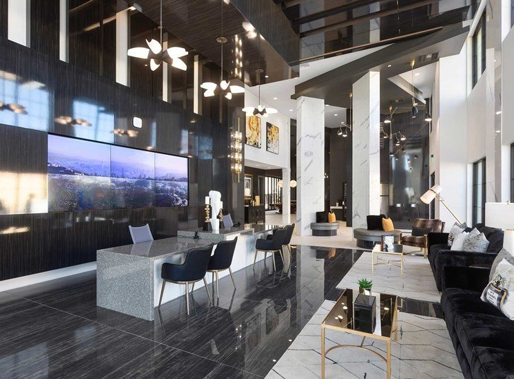 Clubhouse interior with modern black furniture,  marble tables, and gold accents
