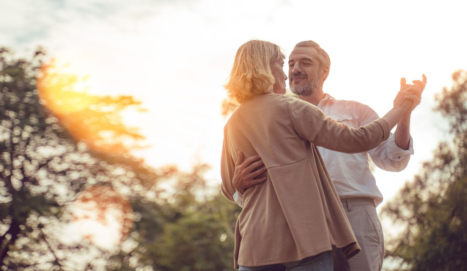 mature couple dancing outside with trees and sun in the background