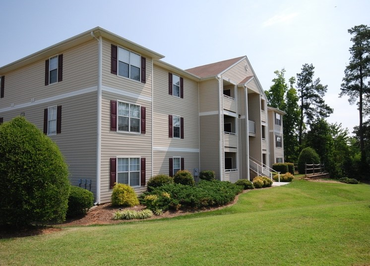 Apartment building exterior with landscaping and large trees in the background