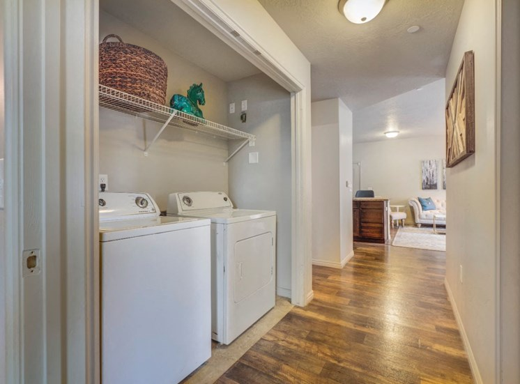 Hallway and Laundry Closet with Full sized Washer and Dryer Under Wire Shelves with Items