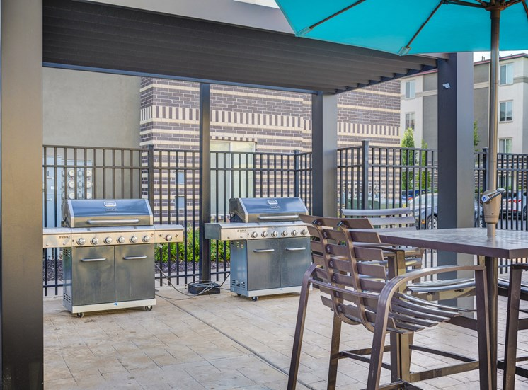 Outdoor grilling stations with tables, chairs and umbrella on a patio