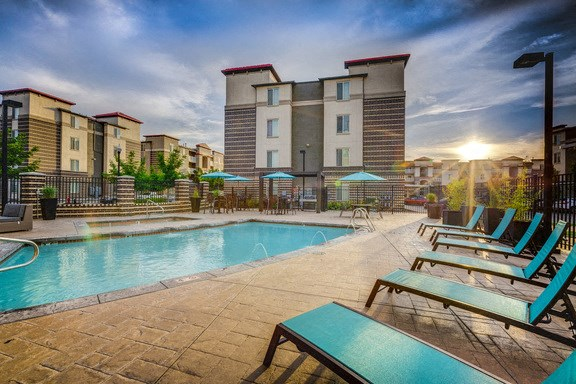 View of sparkling blue pool, a sunset, building exteriors in the background, and blue pool side lounge chairs
