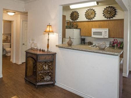 Breakfast bar area located in kitchen with a small hutch decorated with a lamp and decorations located above the microwave