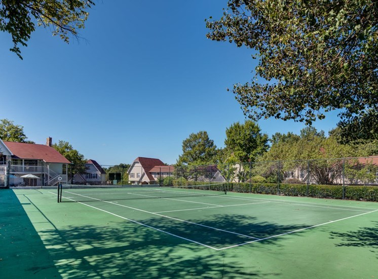 tennis court with apartment buildings in the back ground with trees