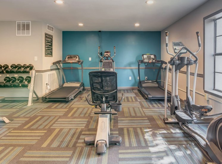 Fitness center with exercise equipment and free weights.