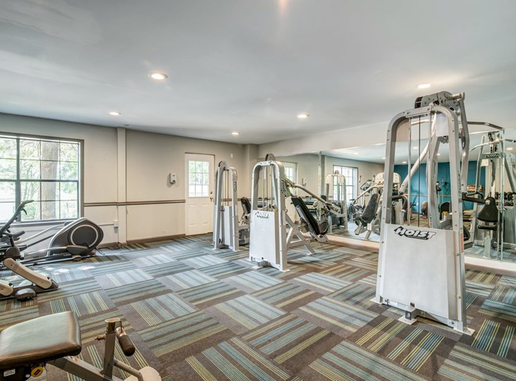 Fitness center with exercise equipment and mirror accent wall