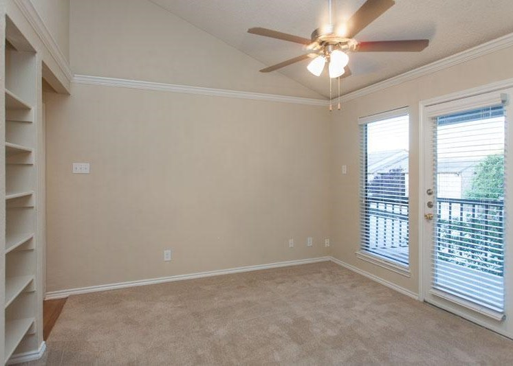Living room with private patio access, ceiling fans, wall to wall carpet