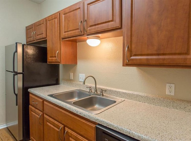 Fully equipped kitchen with brushed nickel appliances, wooden cabinetry, and hardwood style floors