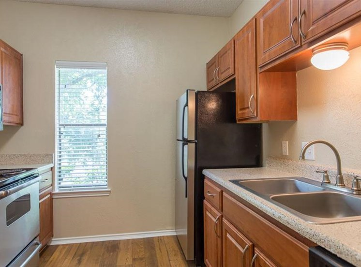 Fully equipped kitchen with hardwood style flooring wooden cabinetry and double basin sink