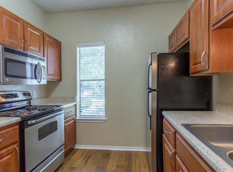 Fully equipped kitchen with double basin sink hardwood style flooring and a window
