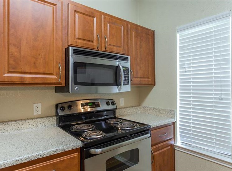 Fully equipped kitchen with wooden cabinetry microwave stove and window