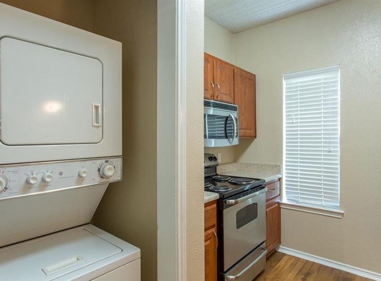 Fully equipped kitchen wooden cabinetry adjacent stackable washer and dryer
