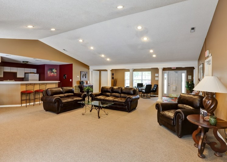 Clubhouse interior with vaulted ceilings and couches with large windows in the background