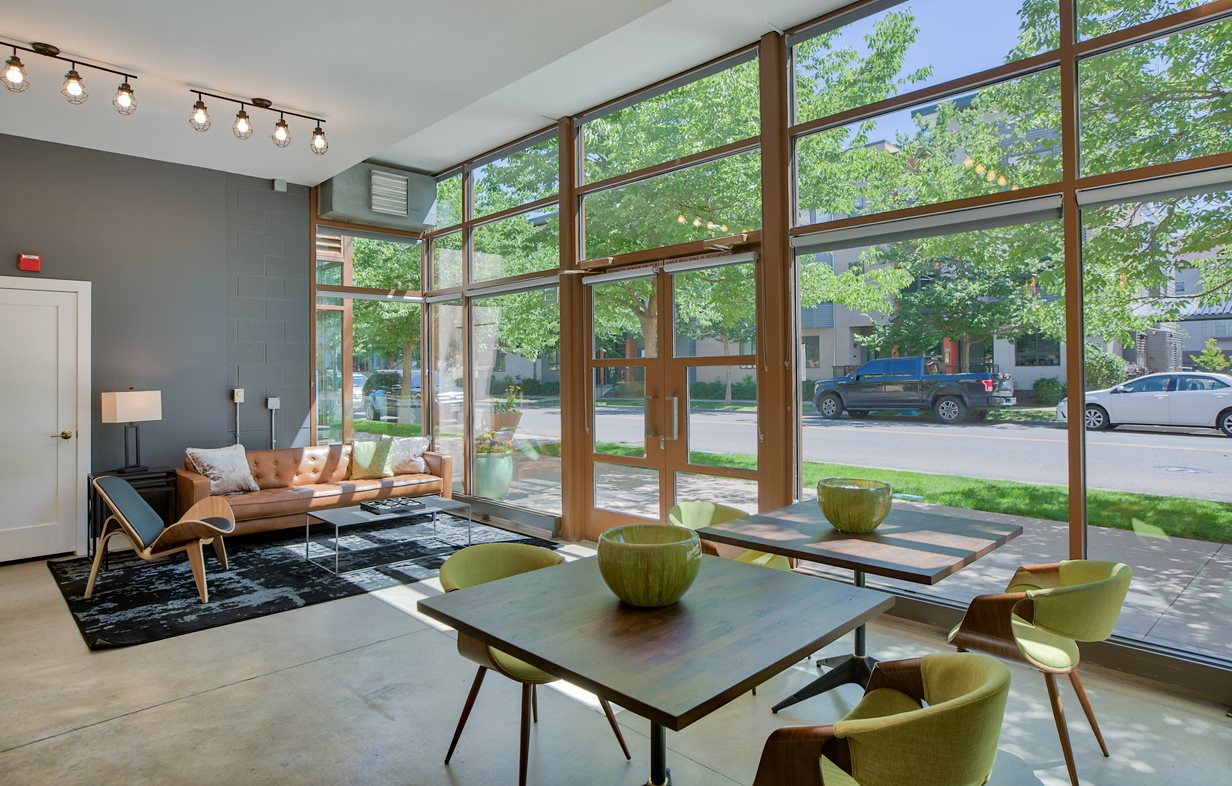 Clubhouse with Wall of WIndows, Contemporary Chairs, Tables and Couch on Area Rug