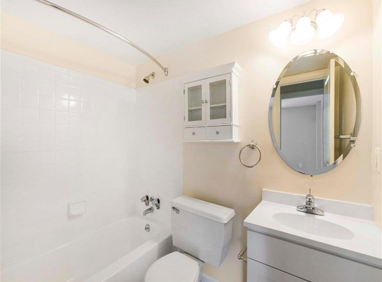 Bathroom with White Cabinets and Counter with Round Mirror