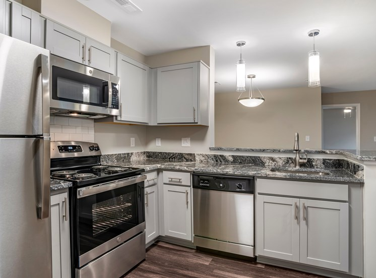 A vacant, renovated kitchen with gray walls, hardwood style flooring, ash gray cabinets with brushed nickel pulls, granite countertops, a single undermount sink with gooseneck faucet, stainless steel appliances, white subway tile backsplash, and a breakfast bar that opens to the dining room. Appliances include refrigerator, built-in microwave, stove/oven combo, and a dishwasher.