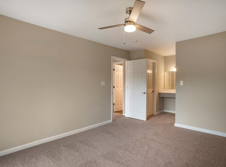 A vacant bedroom with gray walls and white trim, carpet throughout, a white entry door and a vanity area located in the background.