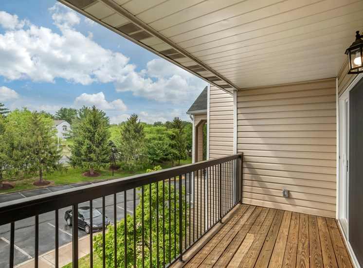 A balcony with wooden deck, black metal railing, opening to the parking lot below, surrounded by trees. The building is made of tan siding and there is a sliding glass door leading to the inside.