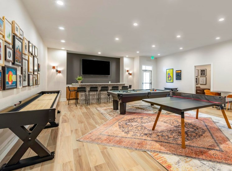 Clubhouse game room with billiard table, ping pong table, arcade game, tables, chairs, and bar with wall mounted television