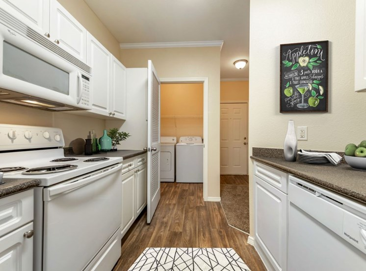 Virtually staged kitchen with hardwood style flooring, white kitchen appliances, floor mat, white cabinetry, and washer and dryer connections