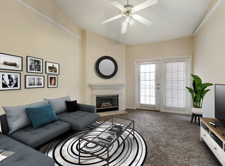 Virtually staged living room with L shaped couch, coffee table, television, wall mounted art, fireplace, multi speed ceiling fan, and private patio access