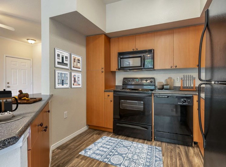 Virtually staged kitchen fully equipped with black appliances, hardwood style flooring, and wall art