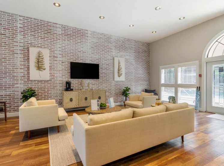 Clubhouse Seating Area with Brick Accent Wall White Couch and White Armchairs Around Mounted TV