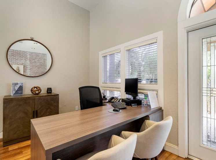 Leasing Office Desk with Chairs in Front of Cabinet and Mirror