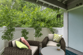 Virtually staged patio with chairs, side table, surrounded by landscaping and outside storage